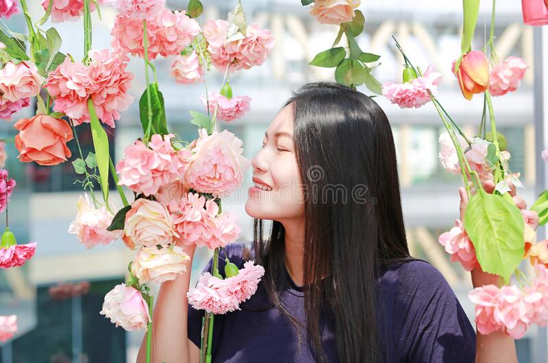 Female smelling upside down sweet flower surrounds the flowering stock photo