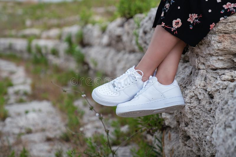 Female sneakers. White female shoes on feet. Sneakers closeup. stock photo