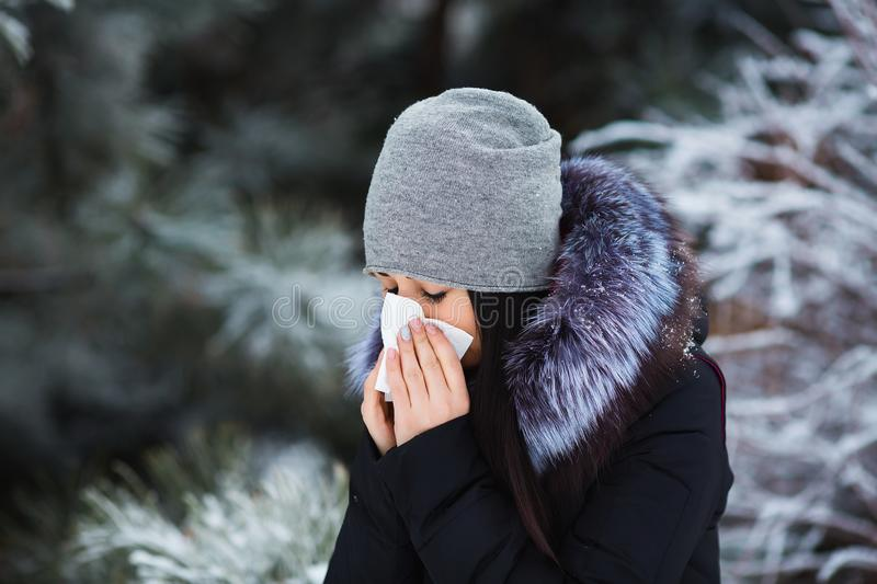 Female sneezing. Pretty young woman has flu and fever in winter day outdoor. royalty free stock photo