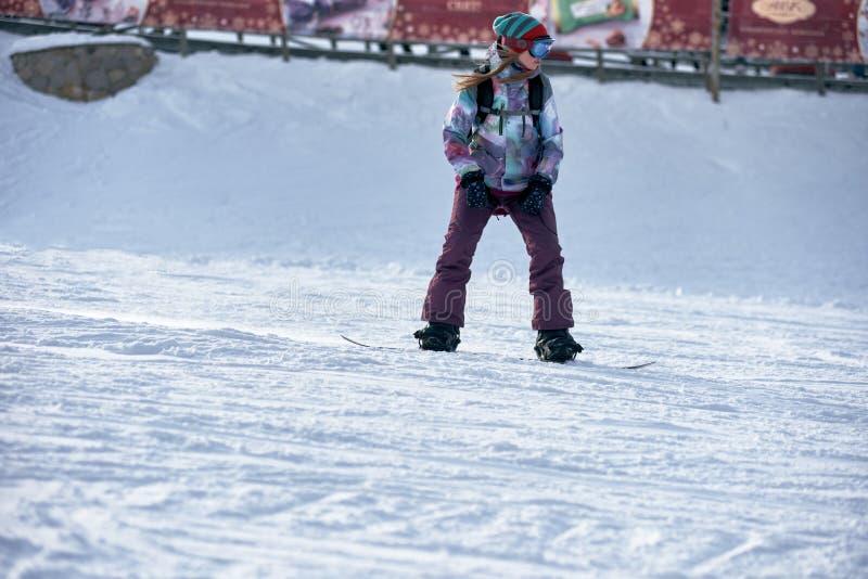 Female snowboarder riding stock image