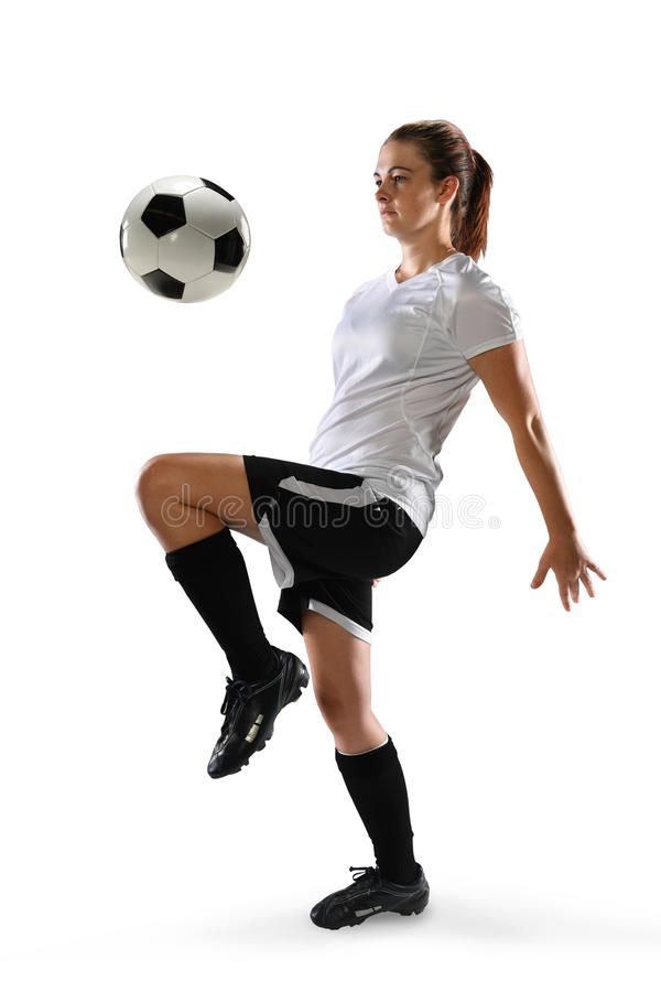 Female Soccer Player Dribbling Ball. Young female soccer player dribbling ball isolated over white background royalty free stock photography