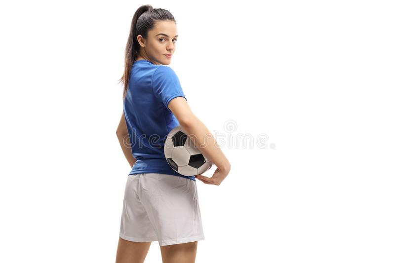 Female soccer player with a football looking over her shoulder stock photo