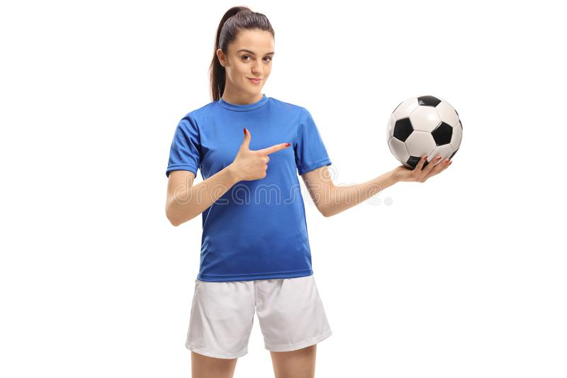 Female soccer player holding a football and pointing stock photography