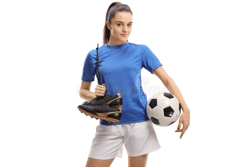 Female soccer player holding a pair of cleats and a football. Isolated on white background royalty free stock image