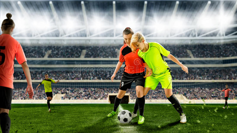 Female soccer players during a scrimmage on a soccer match. Two female soccer players in scrimmage action on a crowded stadium stock photos