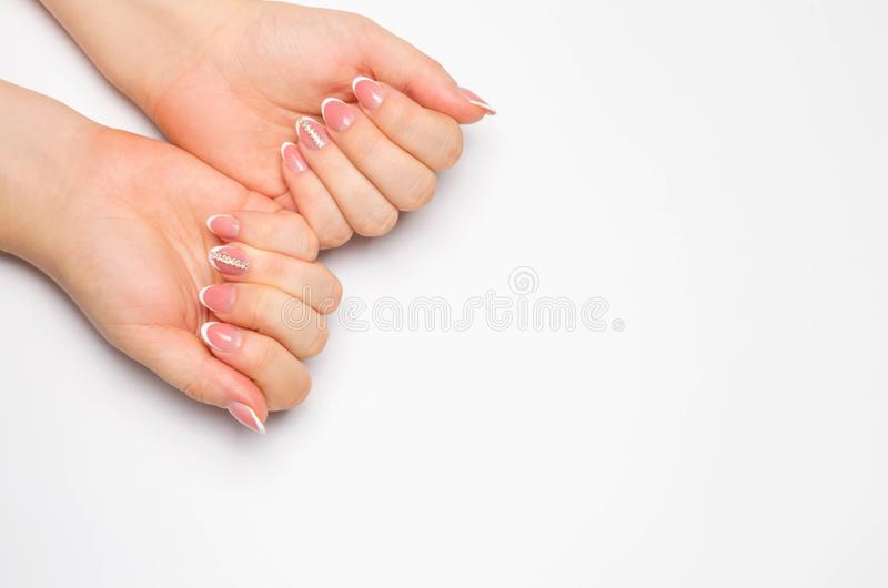 Female soft hands with beautiful french manicure. isolated white background. long nails. place for text. copy space royalty free stock image