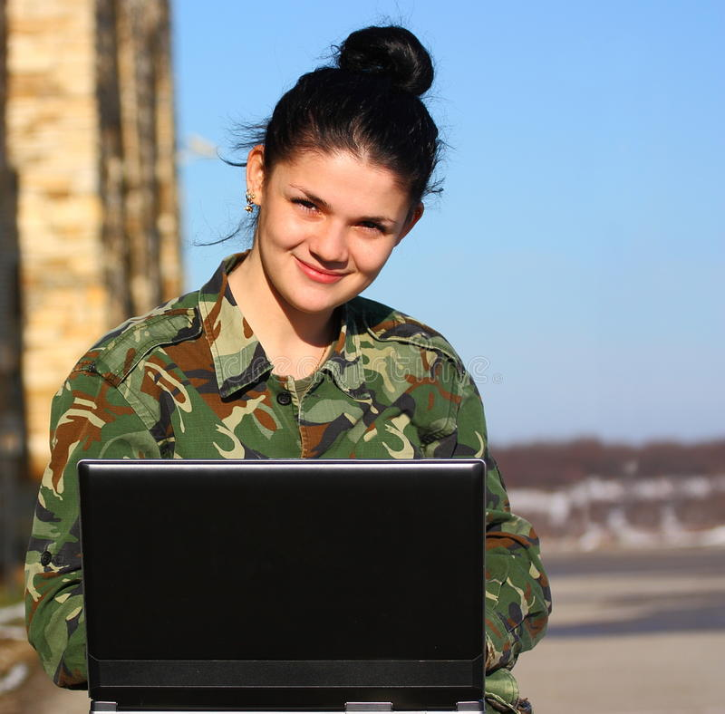 Female soldier. A smiling female soldier working on a laptop outdoor close up shot stock photography