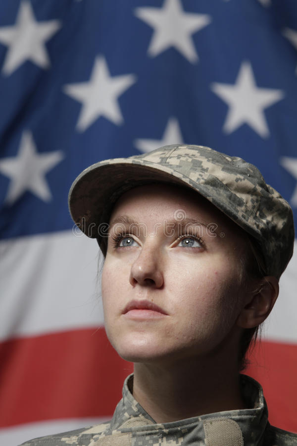 Female soldier in front of US flag looking up, ver. Tical shot royalty free stock images