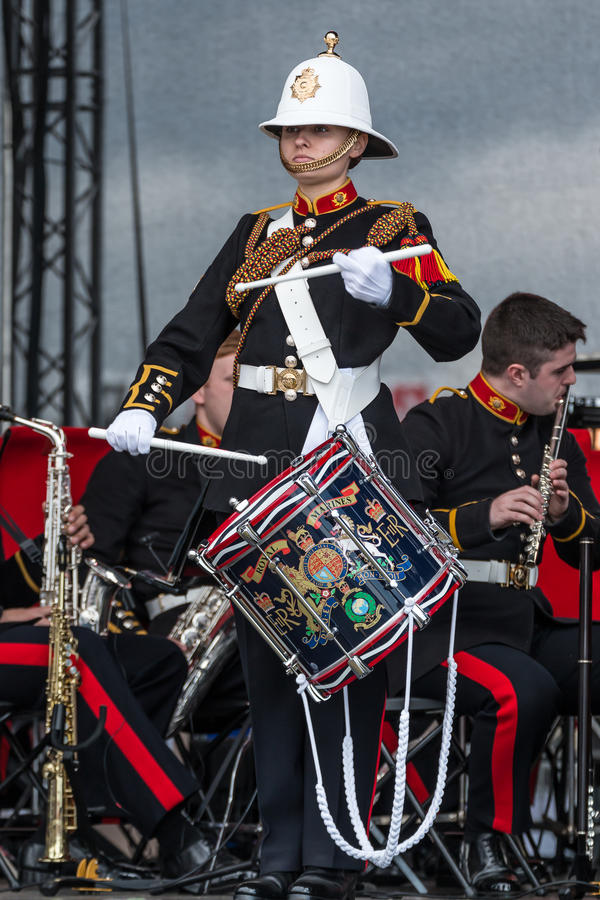Female soldier playing drum in military band, Sunderland. A female soldier from the British Army in dress uniform plays the drum as part of a military band royalty free stock image