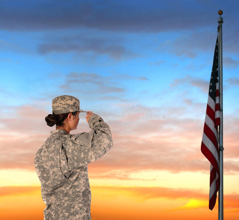 Female Soldier Saluting Flag. Closeup of an American Female Soldier in combat uniform saluting a flag at sunset stock photos
