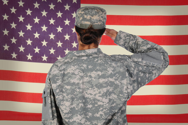 Female Soldier Saluting Grunge Flag. Female Soldier standing in front of and saluting an American flag. Woman is seen form behind only showing her from the waist stock photos