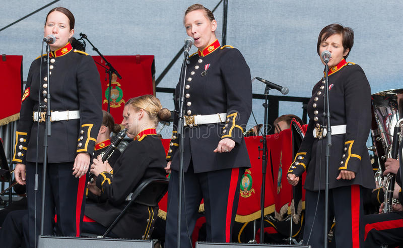 Female soldiers singing in military band, Sunderland. Three female soldiers from the British Army in dress uniform sing as part of a military band. Sunderland stock images