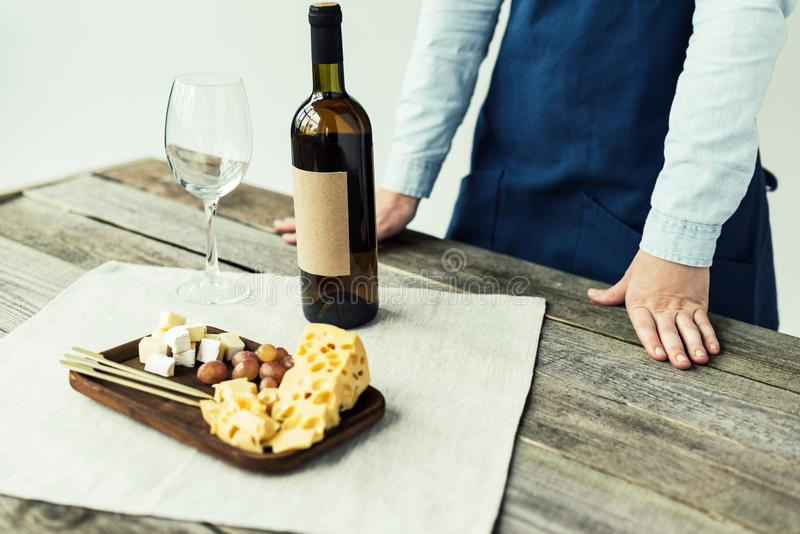 Female sommelier in apron standing at table with wine bottle. And food stock photography
