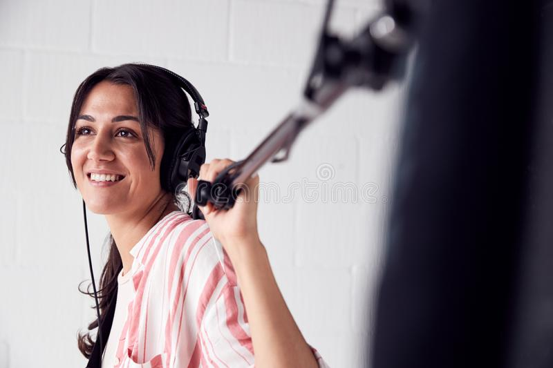 Female Sound Recordist Holding Microphone On Video Film Production In White Studio royalty free stock photography