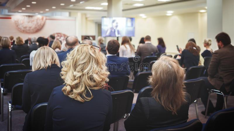 Female speaker giving presentation in lecture hall at university workshop. Rear view of unrecognized participants listening to lec stock images