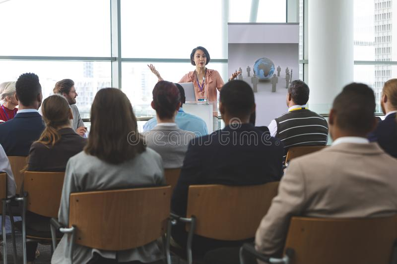 Female speaker with laptop speaks in a business seminar royalty free stock image