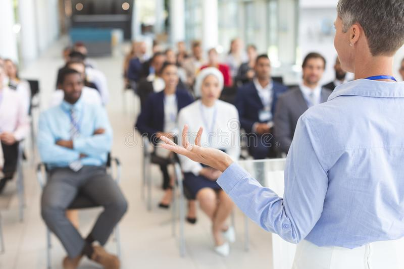 Female speaker speaks in a business seminar. Rear view of Caucasian female speaker speaks to diverse business people in a business seminar in conference royalty free stock photo