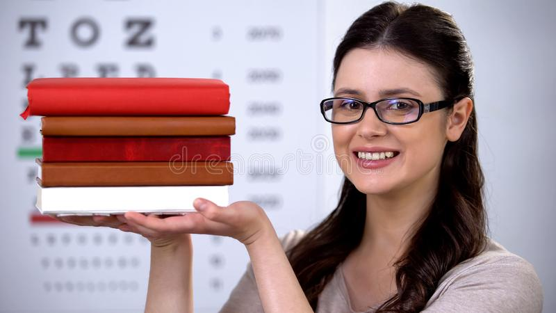 Female in spectacles showing books, oculist student preparing to become doctor royalty free stock photos