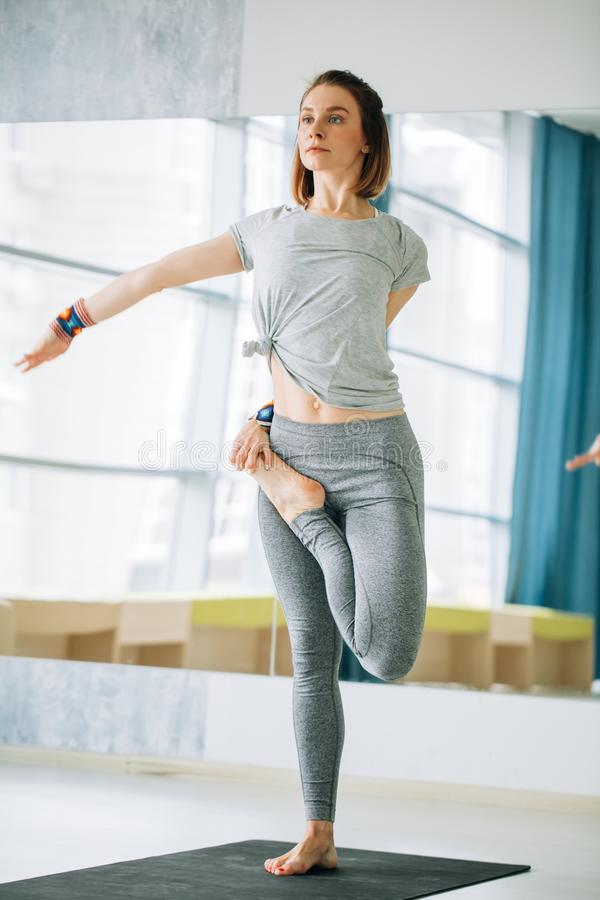 Female in sport clothes performing yoga exercise Tree royalty free stock photo