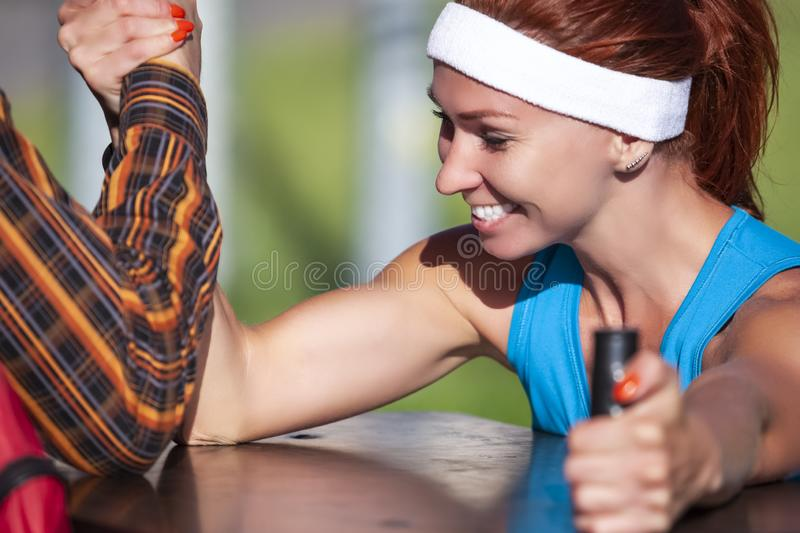 Female in Sport Outfit Playing with Armwrestling Trainer Outdoors. Happy Caucasian Ginger Female in Sport Outfit Playing with Armrestling Trainer Outdoors stock photos
