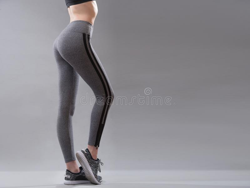 Female sportswear clothes on perfect body, Sneakers and grey leggings pants. stock photo
