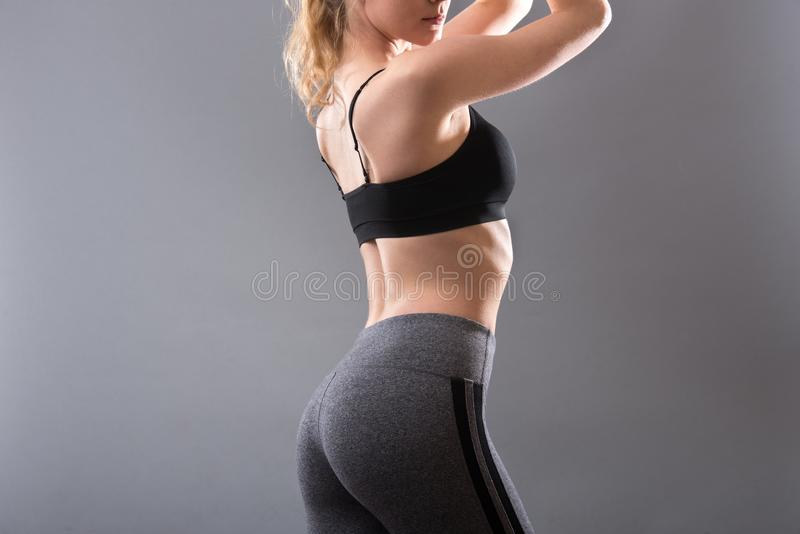 Female sportswear clothes on perfect body. Sport bra and grey leggins pants.  stock images
