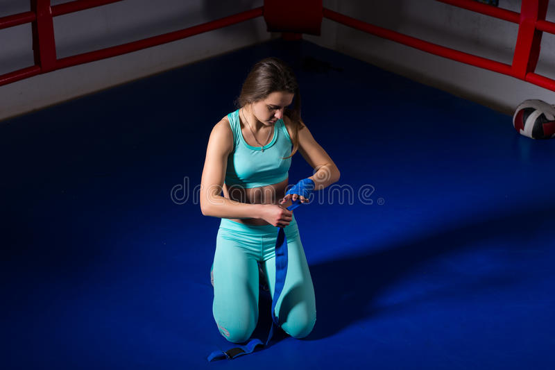 Female sporty boxer preparing bandages for fight. In regular boxing ring in a gym stock photography