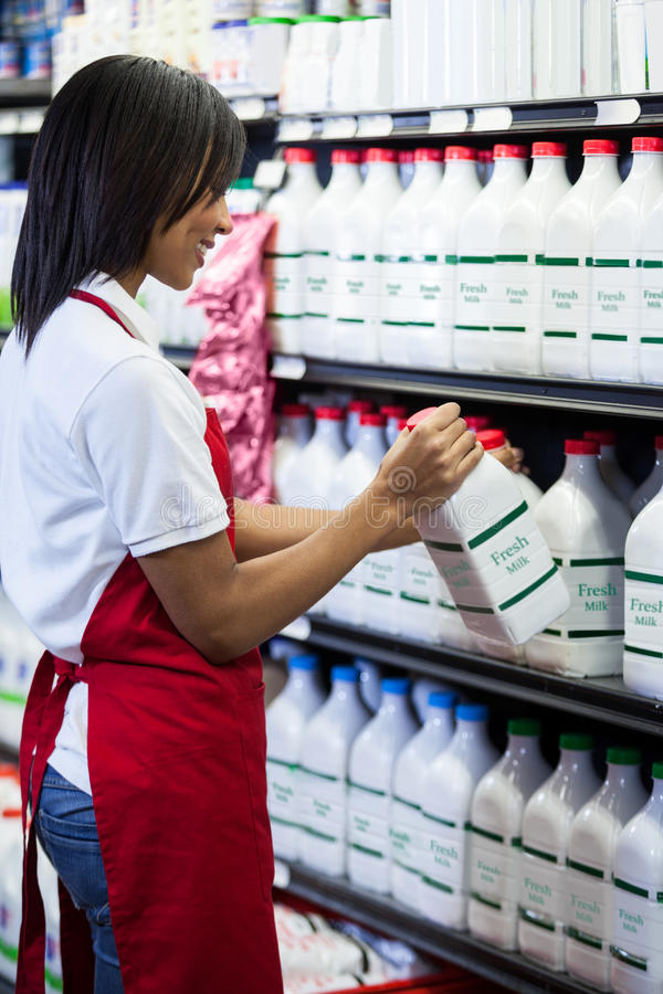 Female staff arranging milk bottle in shelf royalty free stock photos