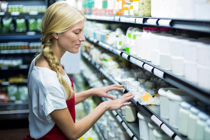 Female staff checking grocery products in shelf royalty free stock photos