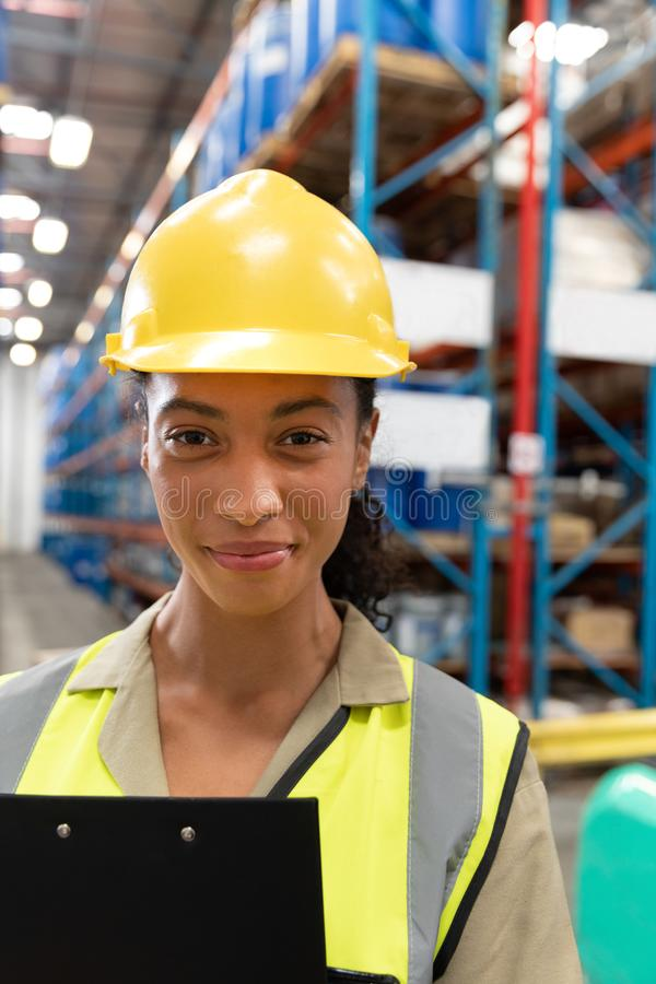 Female staff with clipboard looking at camera in warehouse. Close-up of female staff with clipboard looking at camera in warehouse. This is a freight stock photo