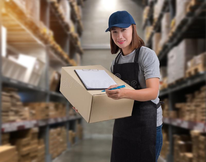 Female staff Delivering products Sign the signature on the product receipt form with parcel boxes. Blurred the background of the warehouse stock images