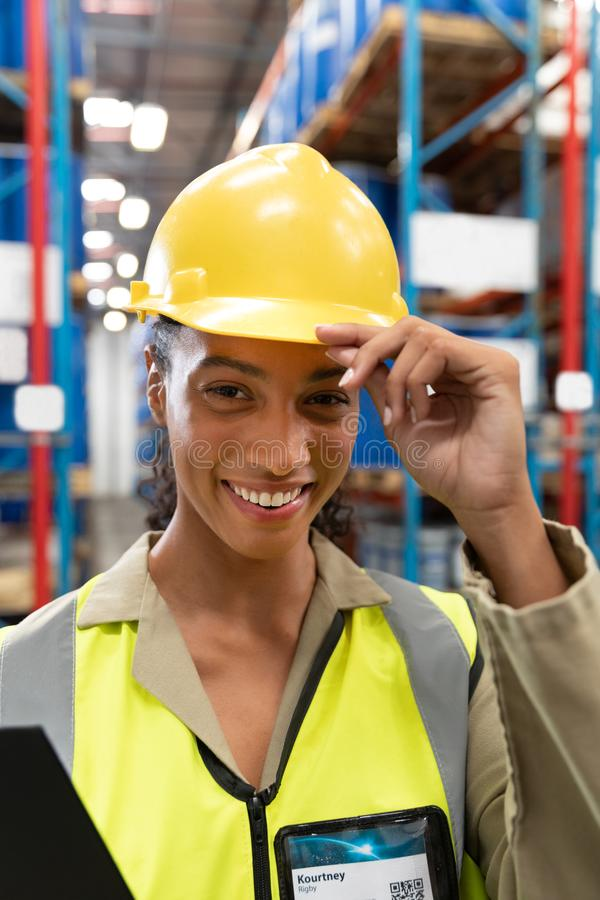 Female staff with hardhat looking at camera in warehouse. Close-up of female staff with hardhat looking at camera in warehouse. This is a freight transportation royalty free stock image