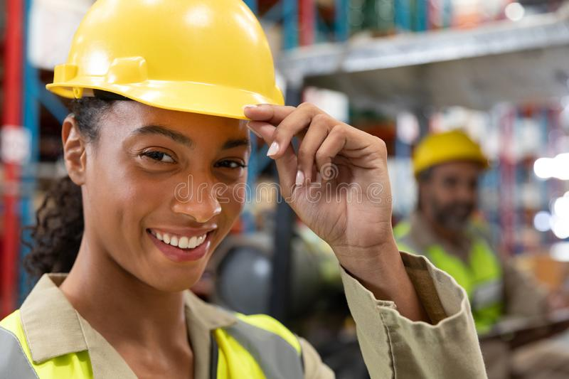 Female staff with hardhat looking at camera in warehouse. Close-up of female staff with hardhat looking at camera in warehouse. This is a freight transportation royalty free stock images