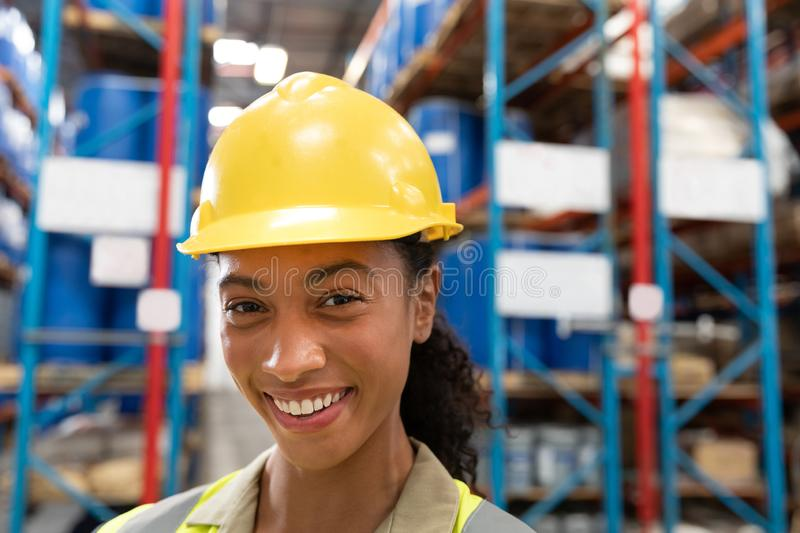 Female staff with hardhat looking at camera in warehouse. Close-up of female staff with hardhat looking at camera in warehouse. This is a freight transportation royalty free stock photography