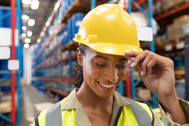 Female staff with hardhat smiling in warehouse. Close-up of female staff with hardhat smiling in warehouse. This is a freight transportation and distribution stock images