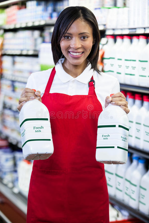 Female staff holding milk bottles in shelf royalty free stock photo