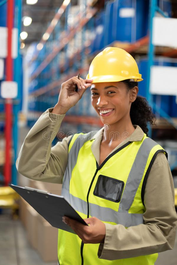 Female staff looking at camera while holding clipboard in warehouse. Happy female staff looking at camera while holding clipboard in warehouse. This is a freight stock photo