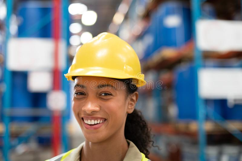 Female staff looking at camera while standing in warehouse. Close-up of female staff looking at camera while standing in warehouse. This is a freight stock photos