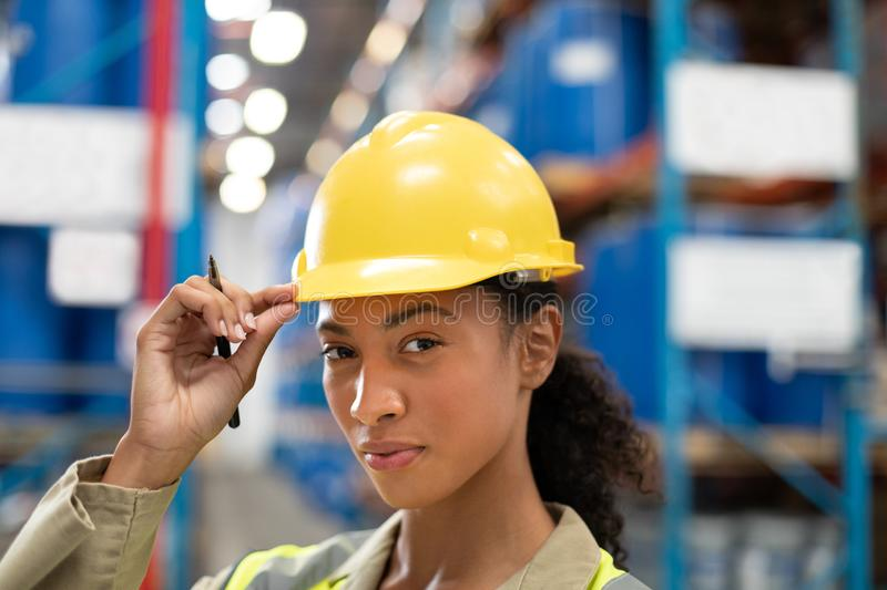 Female staff looking at camera while standing in warehouse. Close-up of female staff looking at camera while standing in warehouse. This is a freight royalty free stock images