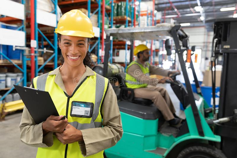 Female staff looking at camera while standing in warehouse. Happy female staff looking at camera while standing in warehouse. This is a freight transportation stock images
