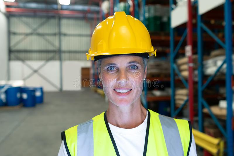Female staff looking at camera in warehouse. Front view of Happy Caucasian female staff looking at camera in warehous. This is a freight transportation and stock images