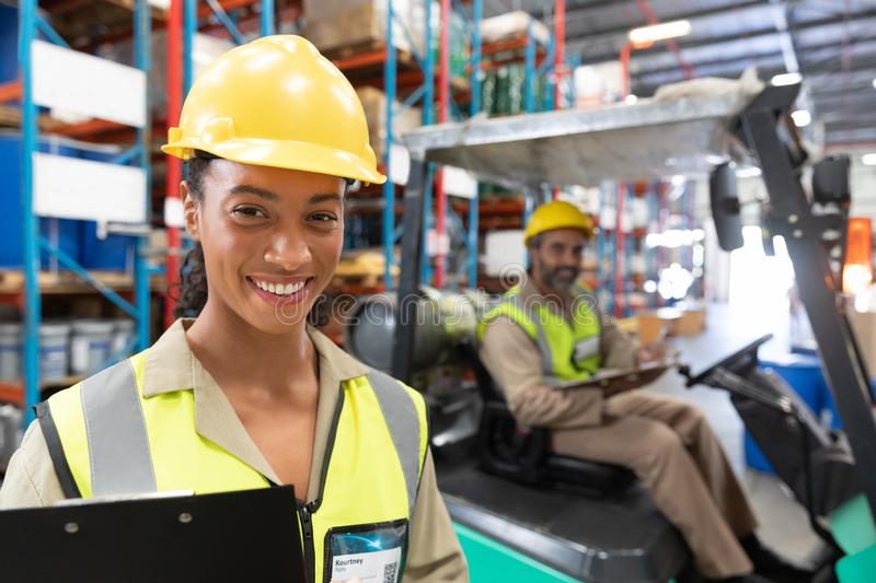 Female staff looking at camera in warehouse. Happy female staff looking at camera in warehouse. This is a freight transportation and distribution warehouse royalty free stock photography