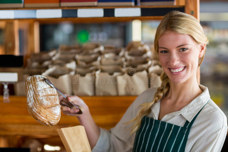 Female staff packing a bread in paper bag stock image