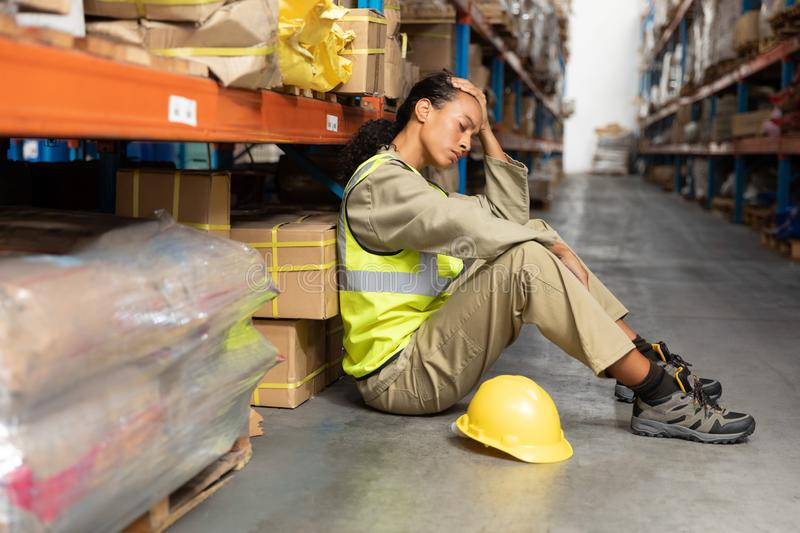 Female staff sitting on floor in warehouse. Tired female staff sitting on floor in warehouse. This is a freight transportation and distribution warehouse royalty free stock images