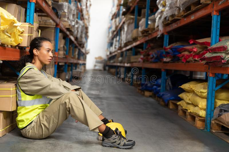 Female staff sitting on floor in warehouse. Tired female staff sitting on floor in warehouse. This is a freight transportation and distribution warehouse stock image