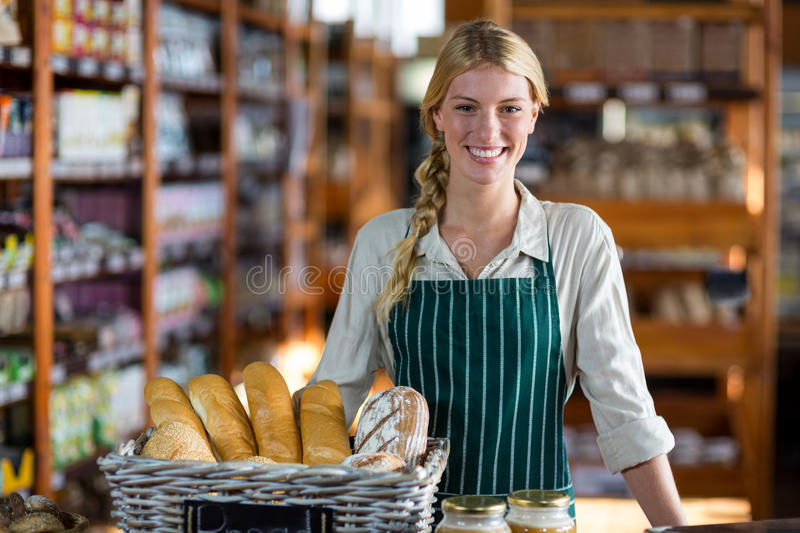 Female staff standing at bread counter royalty free stock images