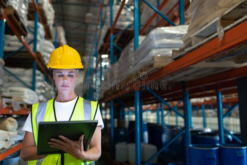 Female staff using digital tablet in warehouse. Front view of Caucasian Attentive female staff using digital tablet in warehouse. This is a freight royalty free stock image