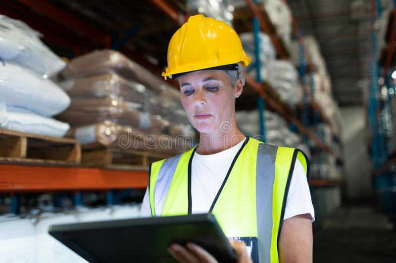 Female staff using digital tablet in warehouse. Front view of Caucasian Attentive female staff using digital tablet in warehouse. This is a freight stock image