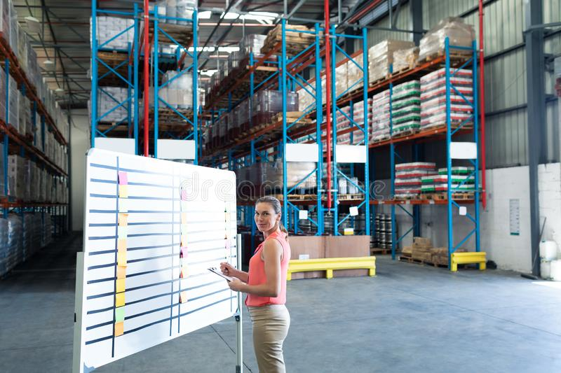 Female staff writing on clipboard near whiteboard in warehouse. Portrait of pretty Caucasian female staff writing on clipboard near whiteboard in warehouse. This royalty free stock photography