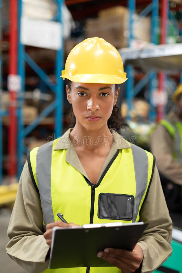 Female staff writing on clipboard in warehouse. Portrait of female staff writing on clipboard in warehouse. This is a freight transportation and distribution royalty free stock photos